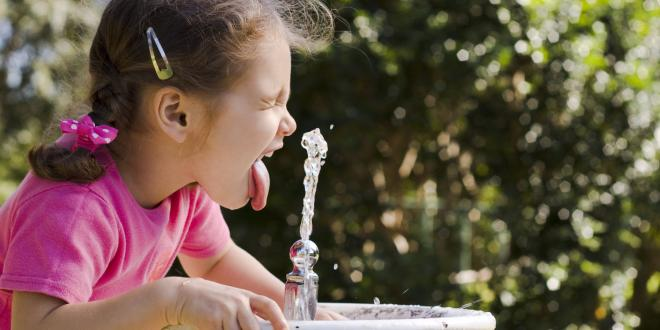 A little girl drinking from a bubbler fountain