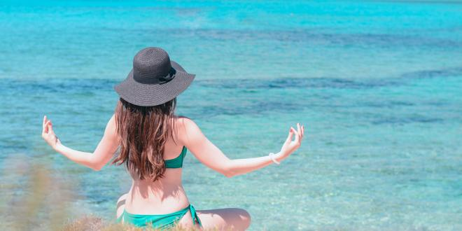 Young woman practices qigong on the beach